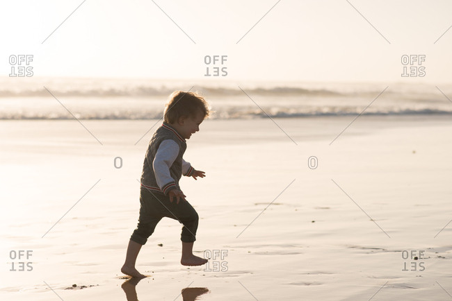 Little laughing boy running on the beach in wet sand