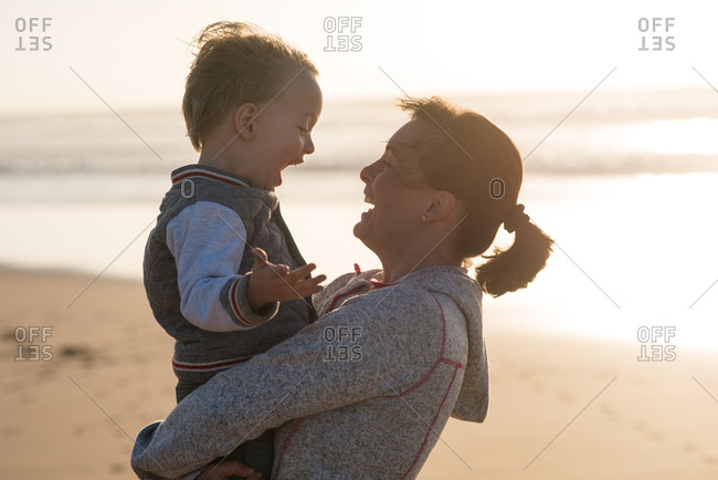 Laughing mother holding her little son on arms on the beach near the ocean during sunset