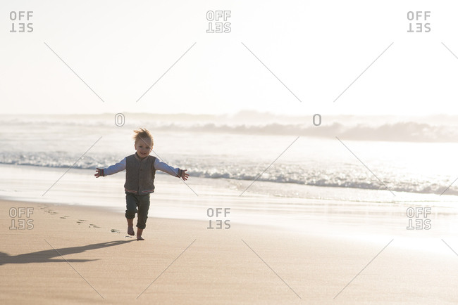 Smiling little boy running on the beach with extended arms