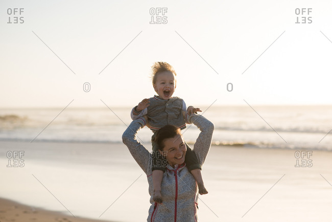 Smiling mother holding her laughing son on shoulders by the sea