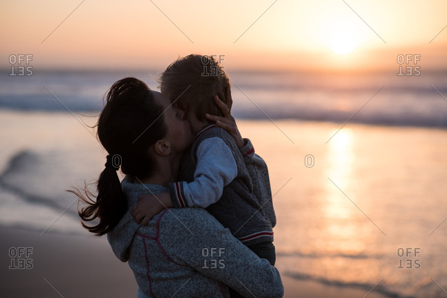 Mother holding little son on arms and kissing him on the beach during sunset