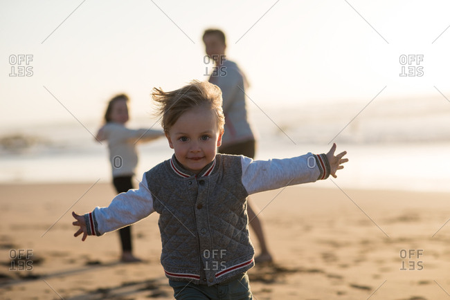 Little boy with big blue eyes running on the beach with mother and sister in the background
