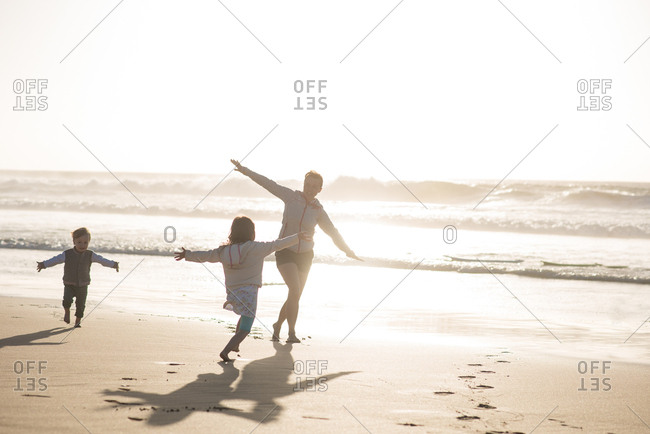 Little son and daughter having fun on the beach by the sea during sunset