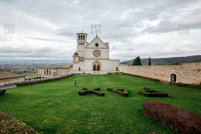 A visitor walking past a hedge formed into the word Pax at the Basilica of Saint Francis of Assisi in Umbria, Italy