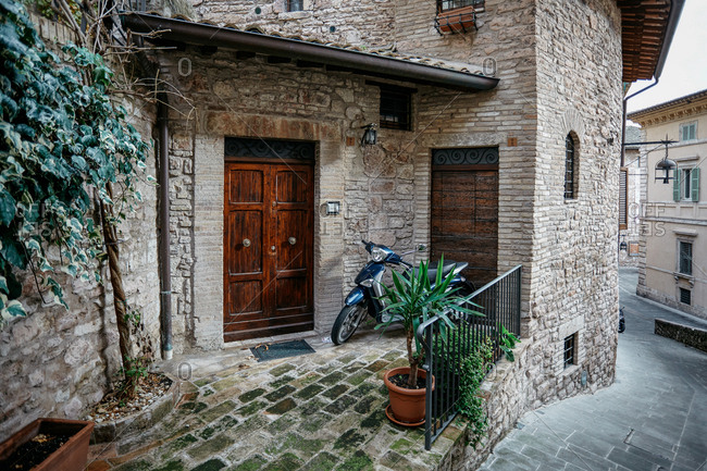 Assisi, Italy - November 16, 2010: Motor scooter parked outside front door of private residence in narrow street