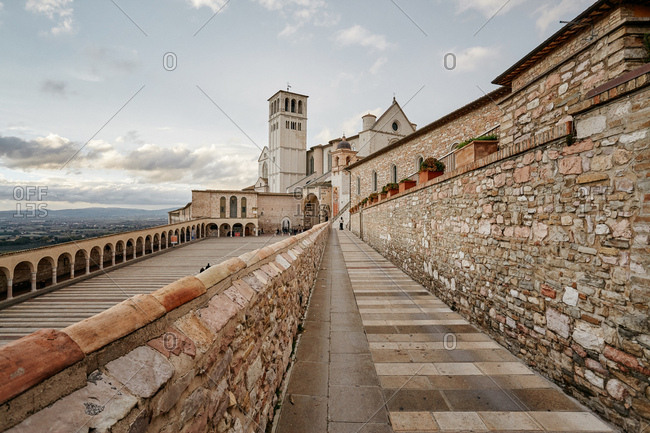 Assisi, Italy - November 16, 2010: Looking down into the courtyard of with the Basilica of Saint Francis of Assisi in the background