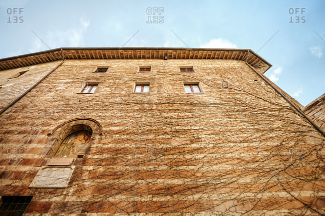 Assisi, Italy - November 16, 2010: Low angle view of recessed religious painting and windows in wall of apartment building