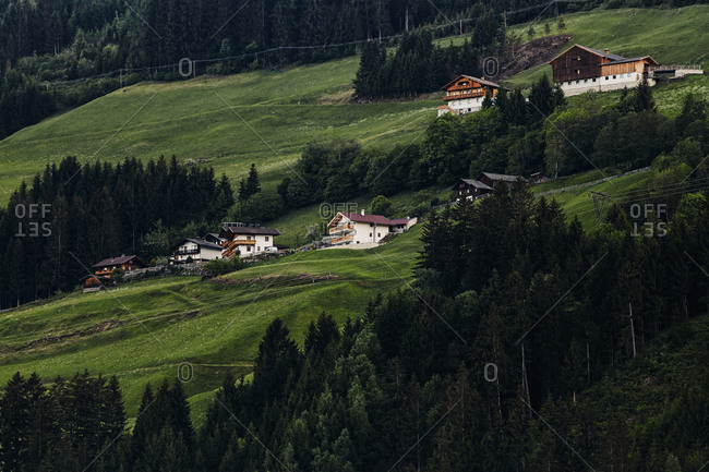 A cluster of traditional houses on the side of a steep hill in Ainet, Austria