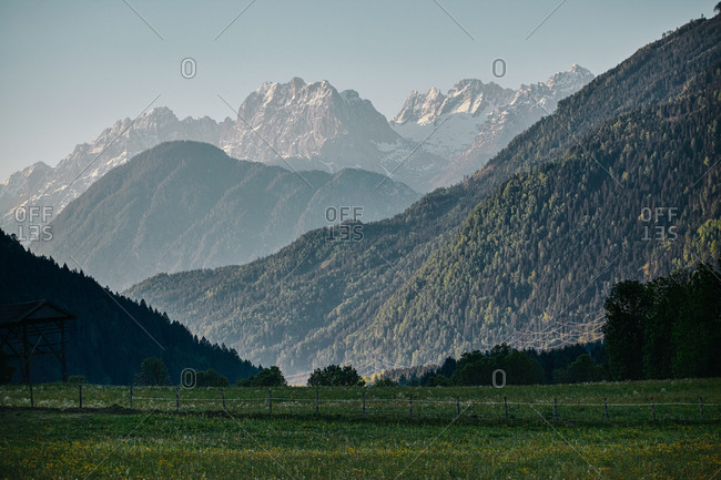 View from bottom of grassy valley looking up at stunning Alpine mountainscape in Austria