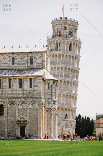 Tourists crowd around the leaning Tower of Pisa with the Cathedral in the foreground