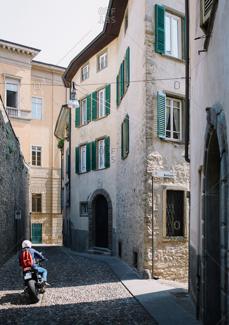 Bergamo, Italy - May 19, 2011: A motorcyclist rides down a densely packed narrow cobbled street