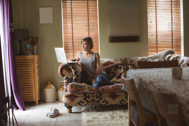 Beautiful woman using laptop on sofa in living room at home