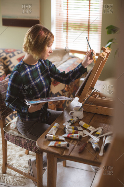 Female artist painting picture on canvas in living room at home
