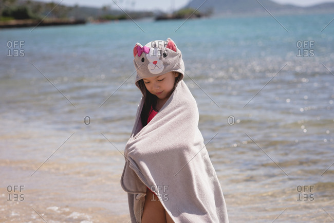 Girl standing with towel in the beach on a sunny day