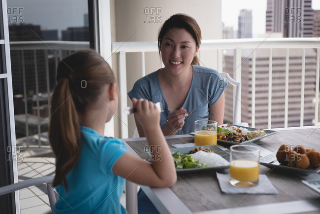 Happy mother and daughter having meal at home