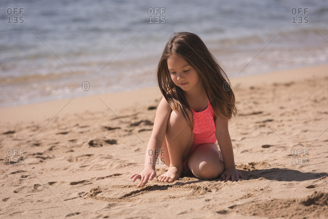 Adorable girl playing on sand in the beach