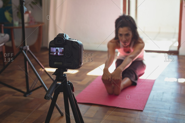 Female video blogger recording video vlog while exercising at home