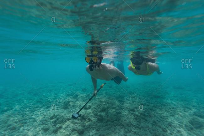Couple snorkeling underwater in turquoise sea