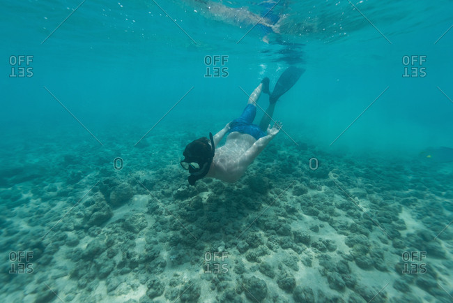 Man snorkeling underwater in turquoise sea