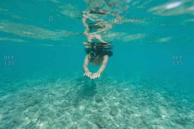Woman snorkeling underwater in turquoise sea