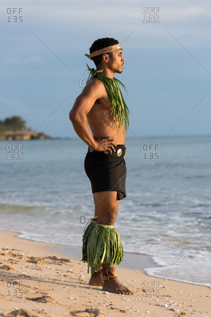 Thoughtful male fire dancer standing with hands on hip at beach