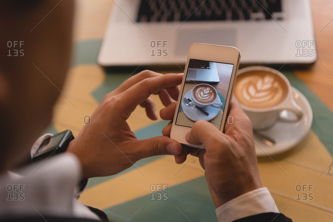 Close-up of businessman clicking photo of coffee in coffee shop