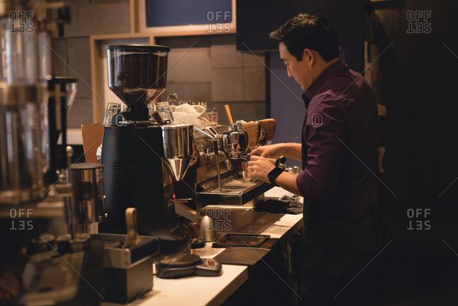 Male waiter preparing coffee in coffee shop