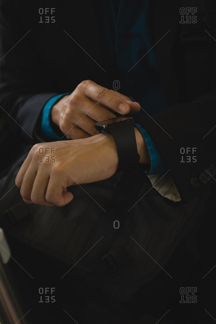 Mid section of businessman using smart watch in bus