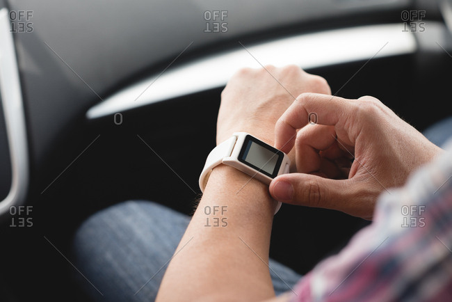 Mid section of man using smart watch in a car
