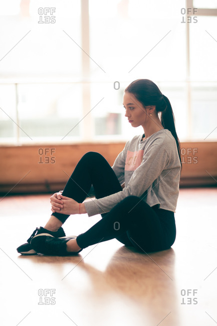 Thoughtful female dancer relaxing in dance studio