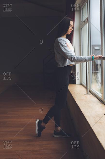 Thoughtful female dancer looking through window in dance studio