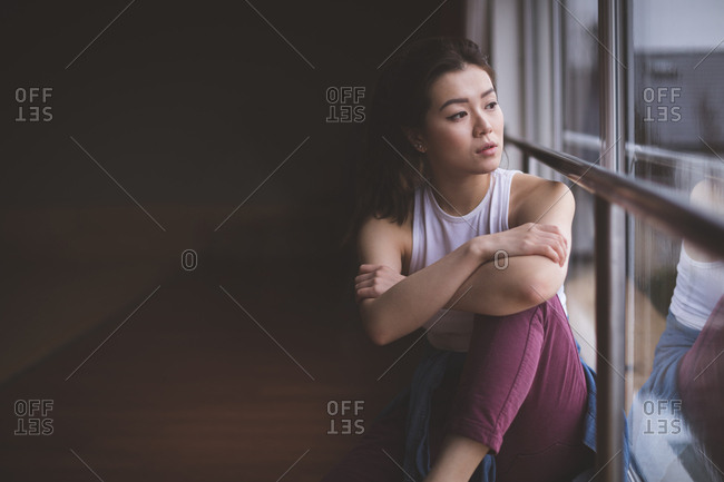 Thoughtful female dancer looking through window in dance studio