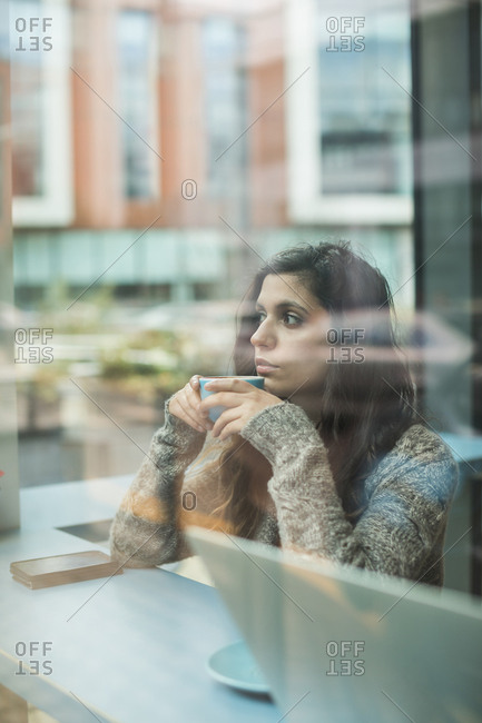 Thoughtful woman having coffee in coffee shop
