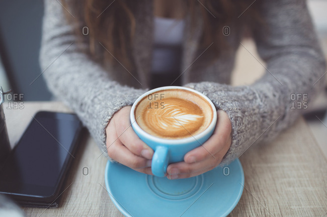 Mid section of woman holding coffee cup in coffee shop