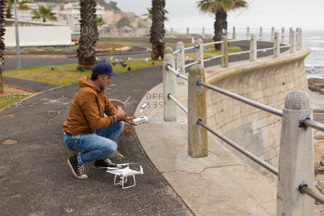 Man operating a flying drone near sidewalk