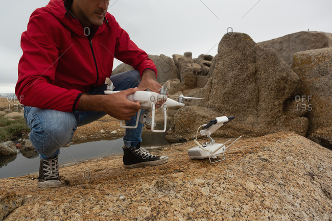 Man operating a flying drone on a rock
