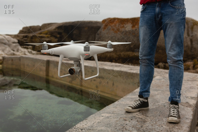 Man operating a flying drone in countryside
