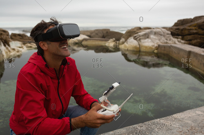 Man operating a flying drone while using virtual reality headset in countryside