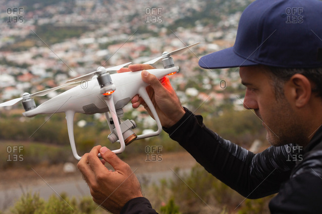 Close-up of man holding a flying drone