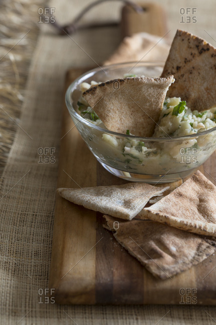 Fresh dip and pita chips on rustic kitchen counter