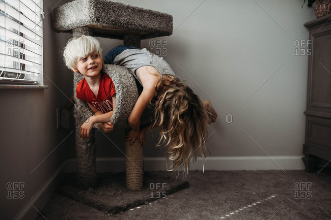 Children play around on a cat scratching post