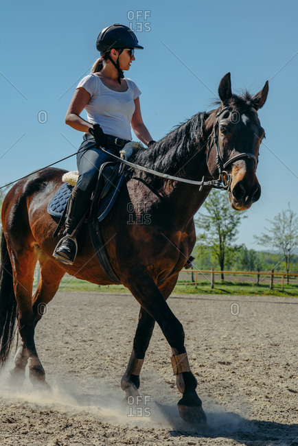 Young woman riding a horse in equestrian center on a sunny day