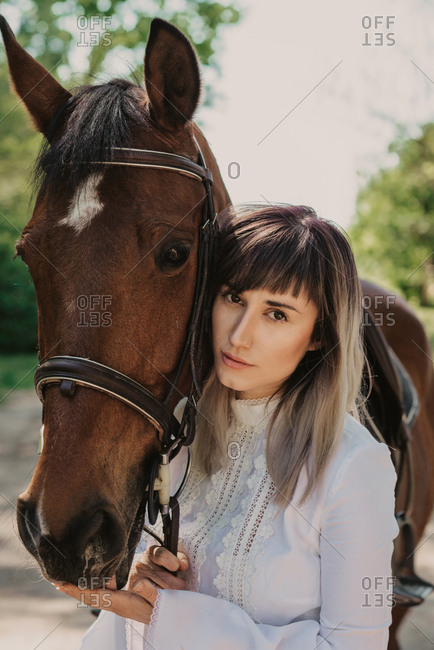 Portrait of woman in white summer dress next to her horse