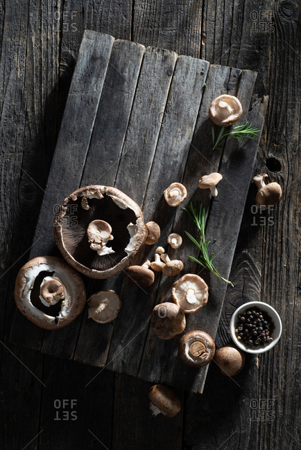 Raw mushrooms with fresh herbs on a rustic farmhouse table