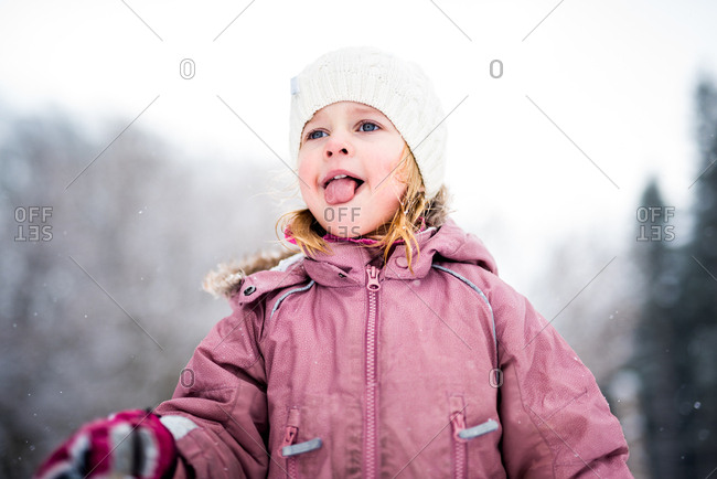 Girl catching snowflakes on her tongue