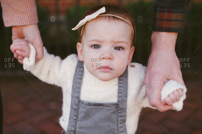 Parents hold a child's hands
