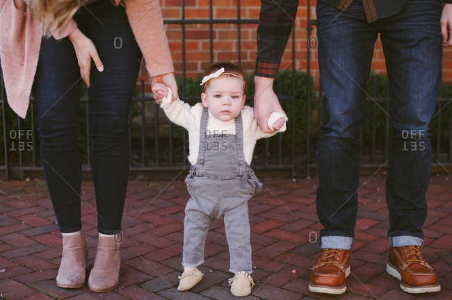 Parents hold their baby girl's hands