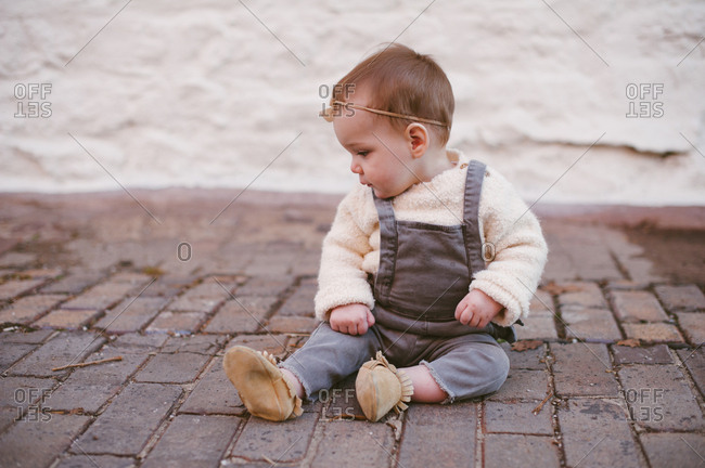 Portrait of a baby girl in overalls on a brick sidewalk