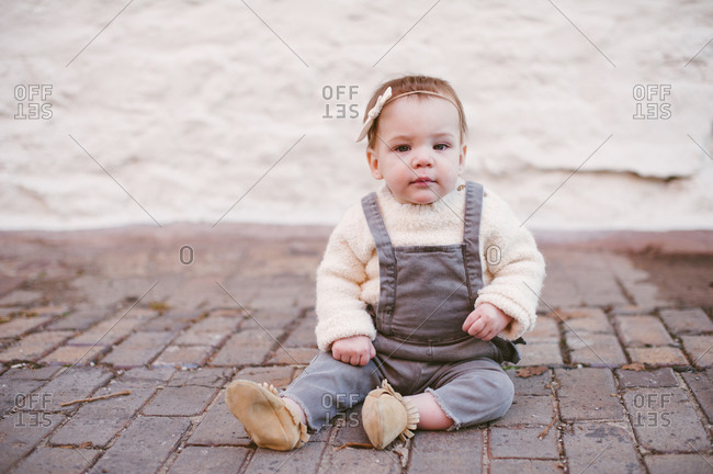 Portrait of a baby girl in overalls and a bow on a brick sidewalk
