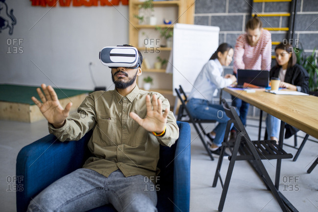 Young south Asian man using VR headset while colleagues work on laptop in background